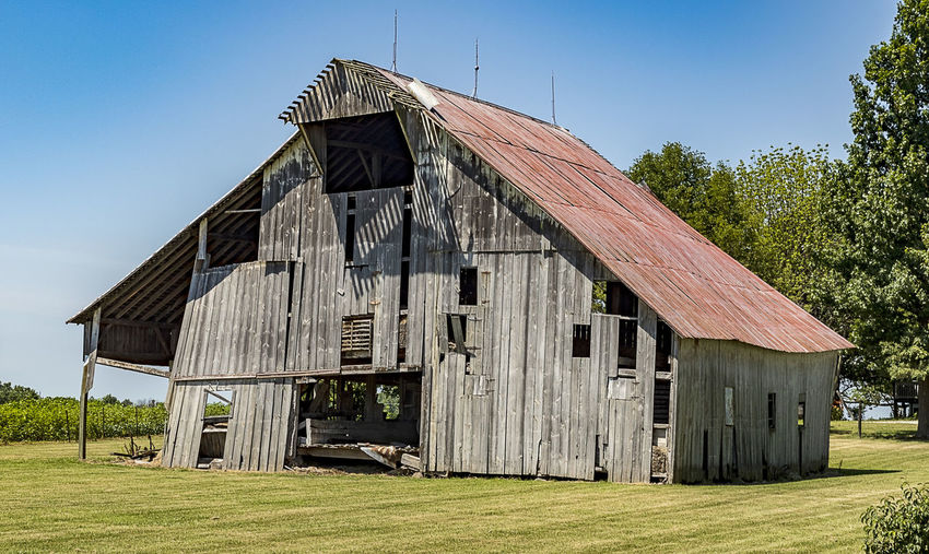 An aging and decaying wooden barn. Architecture Built Structure Building Exterior Wood - Material Nature Agricultural Building Grass Sky Day Barn Farm Landscape Rustic Clear Sky Outdoors Americana Rural Decay Wooden Aging Decaying Countryside Country Life Trees