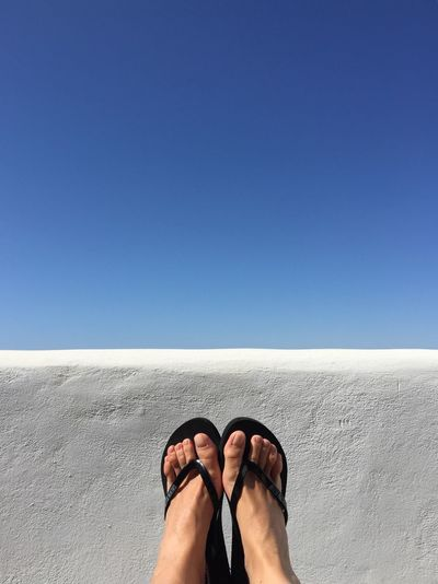 Low section of woman legs against blue sky