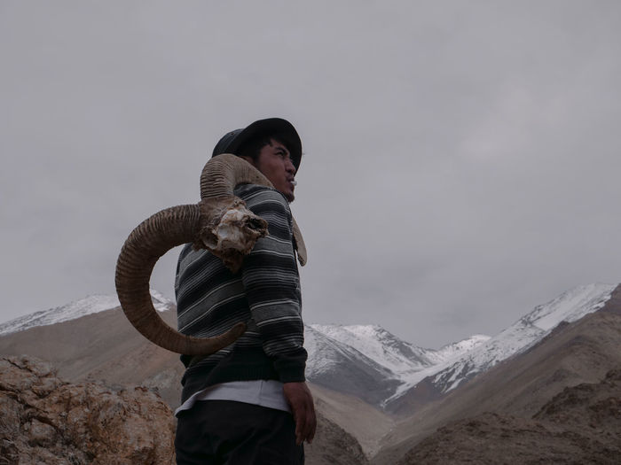 Side view of young man carrying horns while standing on mountain against cloudy sky