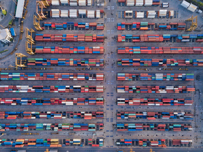 Aerial top view of container cargo ship in the export and import business and logistics international goods in urban city. Shipping cargo to the harbor by crane. Container Shipping  Logistics Ship Cargo Export Business International Goods Transportation Architecture Building Exterior Built Structure Aerial View City Day Travel Destinations Mode Of Transportation No People Order In A Row Outdoors Travel Building Industry Development High Angle View Large Group Of Objects Apartment