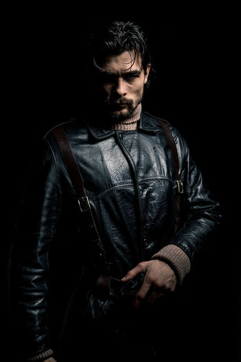 A man in a black leather coat and a brown sweater. Mercenary with a gun. He wears medium-length hair, a mustache and a beard. Hair is wet and glisten in the rays of light. Brutal look like a comic book hero. Pensive look, serious guy. Low key portrait. Silhouette of a man on a black background. Selective lighting. Studio photography. Portrait Black Leather Serious One Person One Man Only Gun Studio Shot Indoors  Young Adult Young Men Standing Front View Black Background Waist Up Facial Hair Men Looking Communication Beard Technology Casual Clothing Three Quarter Length Wireless Technology Holding