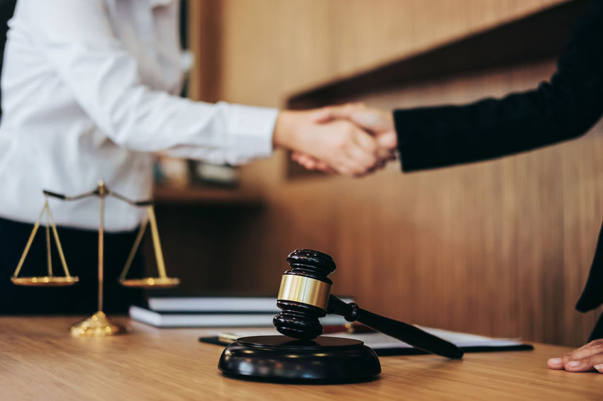 Collaboration Lawyer Adult Arts Culture And Entertainment Balance Barrister Counselor Fairness Gavel Hand Handshake Human Body Part Human Hand Indoors  Judgement Legal Legislation Men People Selective Focus Shaking Hands Standing Two People Verdict Wood - Material