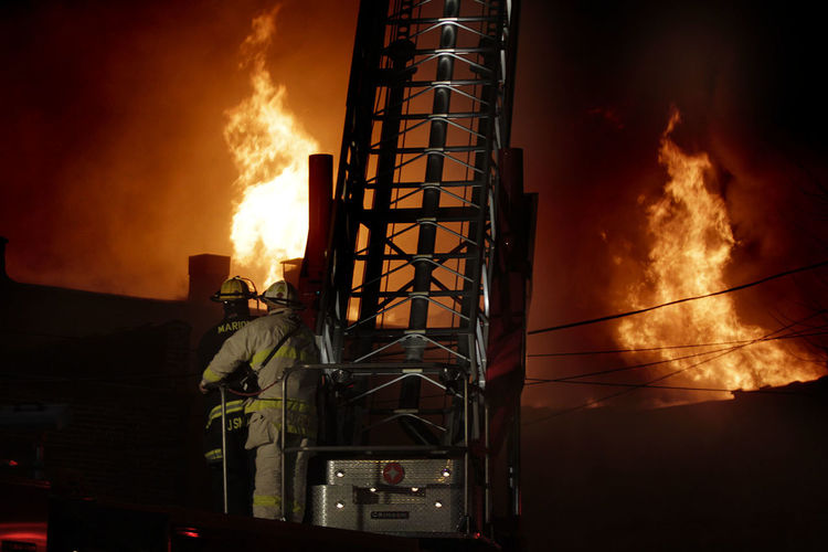 Rear view of firefighters by ladder against fire at night