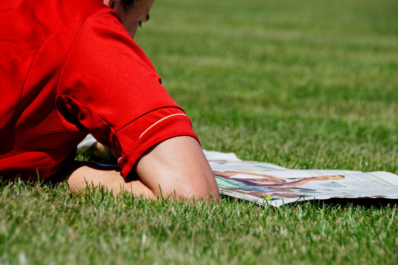 Close-up of man reading newspaper on field