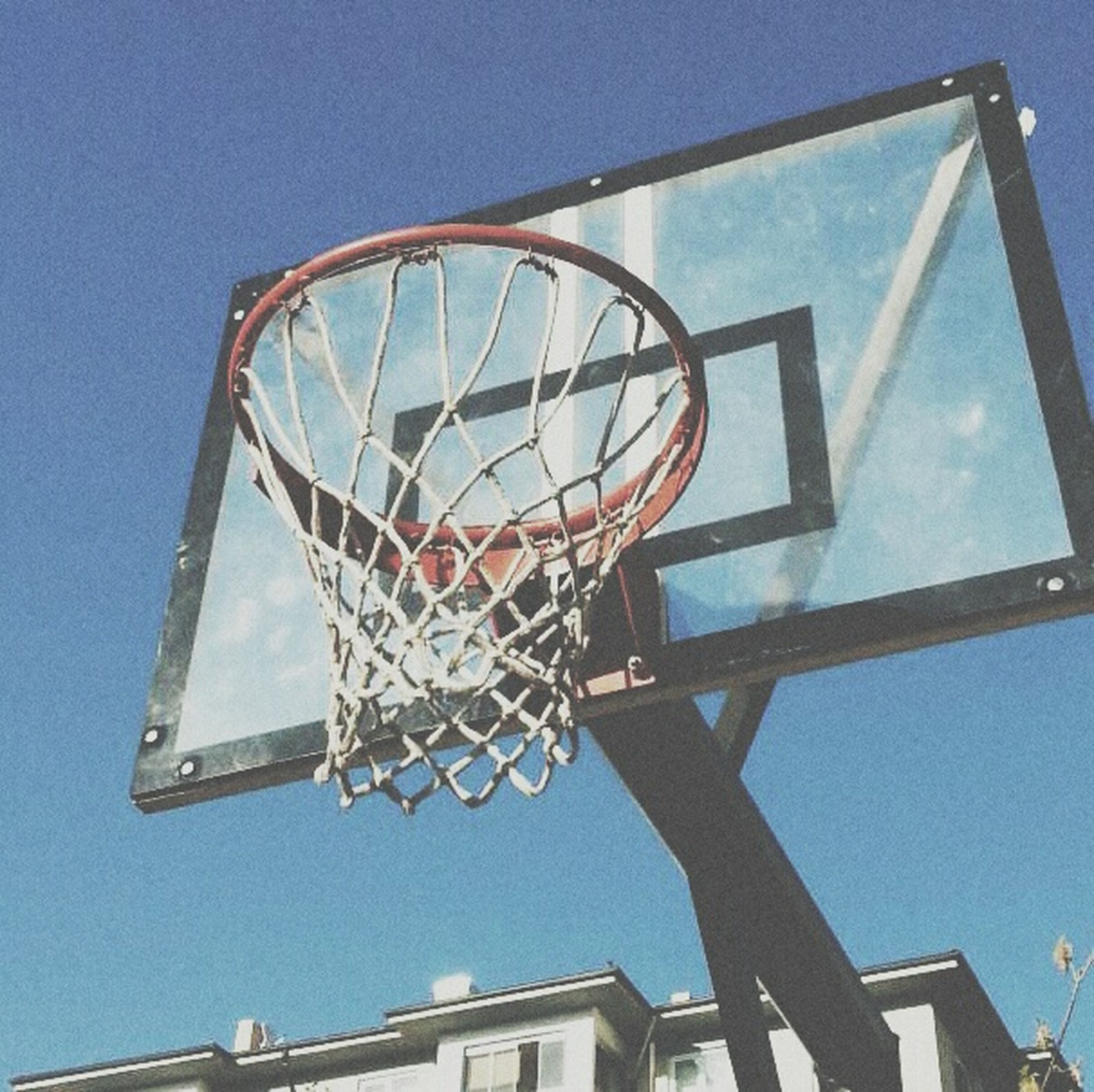 low angle view, built structure, architecture, building exterior, blue, clear sky, sky, day, hanging, window, no people, outdoors, sunlight, lighting equipment, metal, building, basketball hoop, geometric shape, lantern, circle