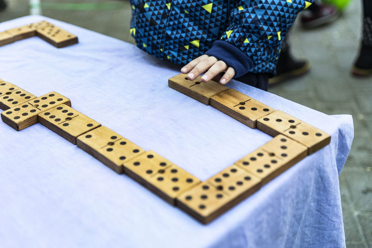 Domino Domino One Person Focus On Foreground Day Real People Leisure Activity Close-up Human Body Part Text Wood - Material Relaxation Indoors  Holding Leisure Games Selective Focus Childhood Lifestyles Midsection Playing Jeans