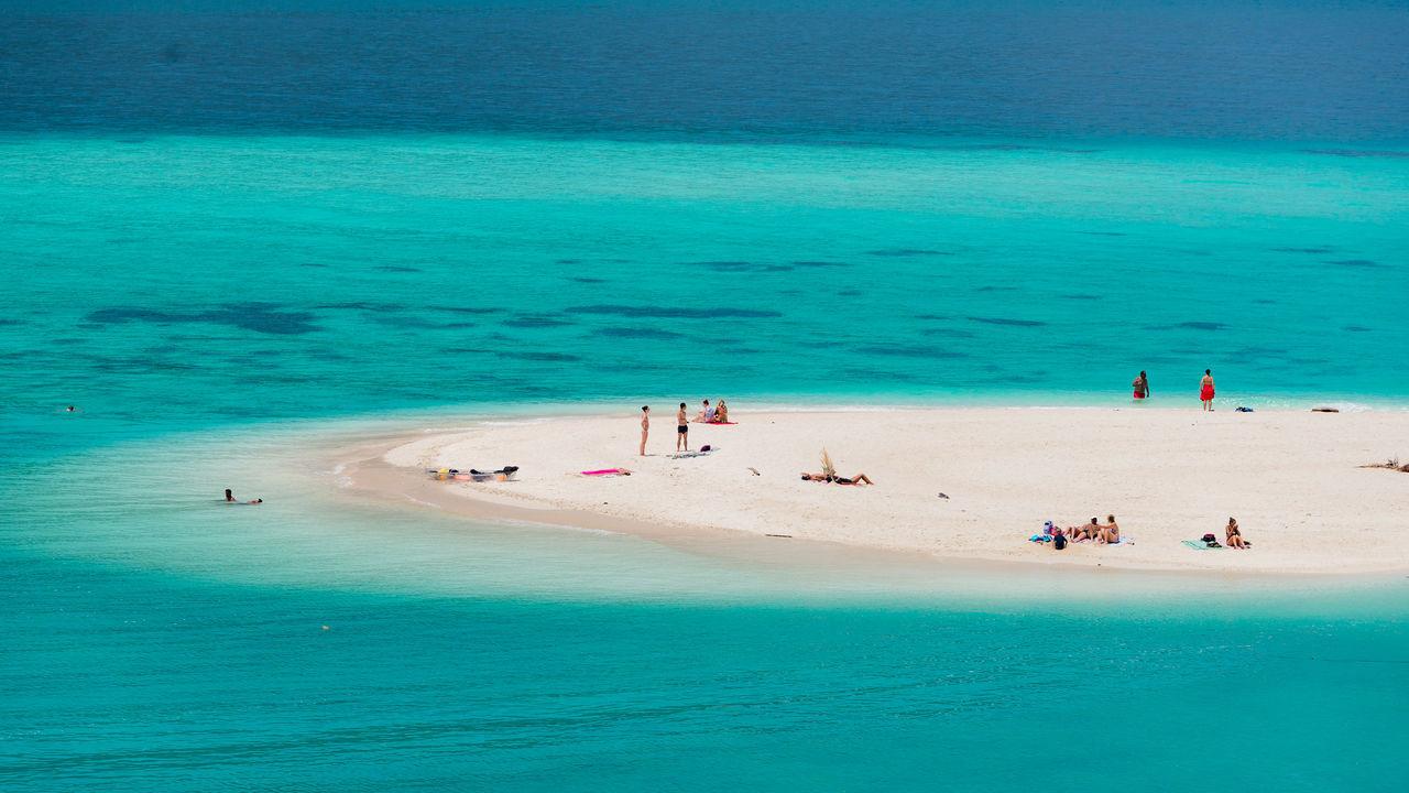 People on beach against blue sea