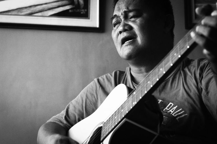Musician Singing While Playing Guitar At Home