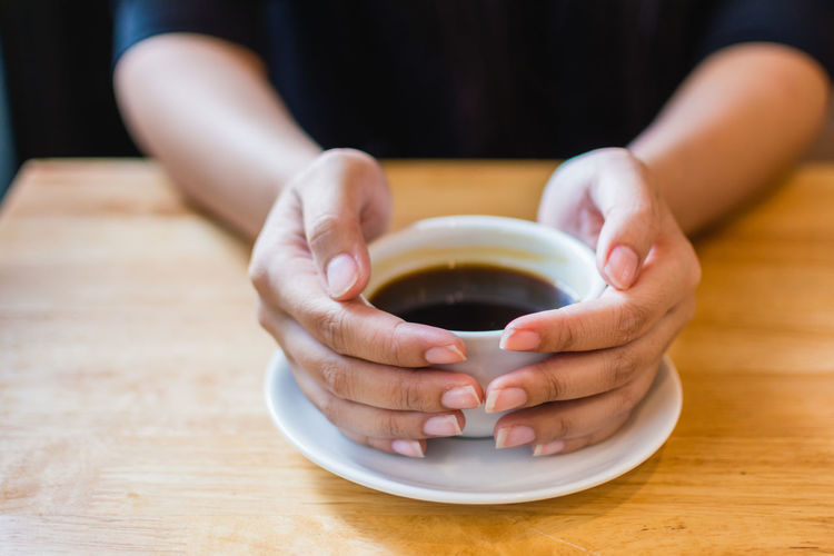 Close-Up Of Hands Holding Coffee Cup