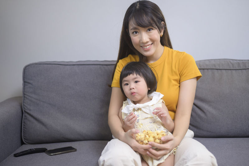 Portrait of mother and baby sitting on sofa