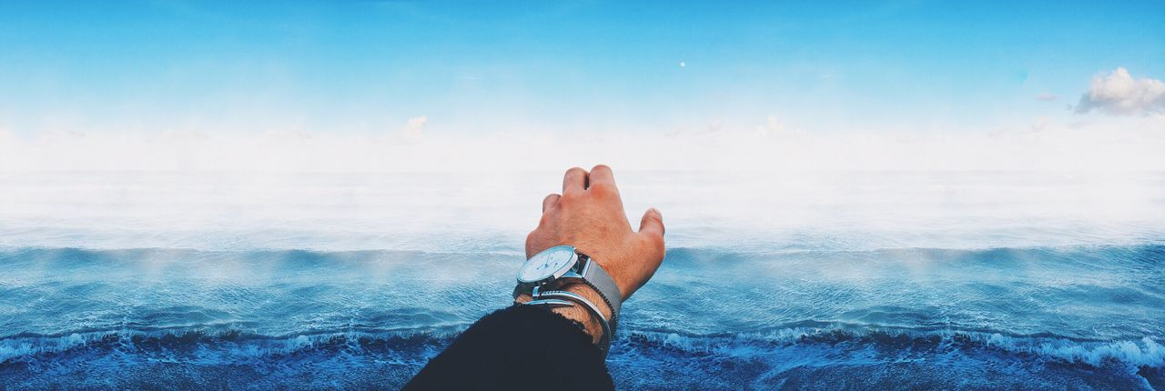 Hand of a man against wavy sea