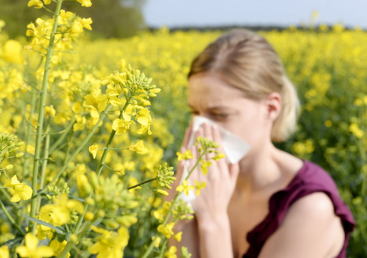 Woman cleaning nose by yellow flowering plants