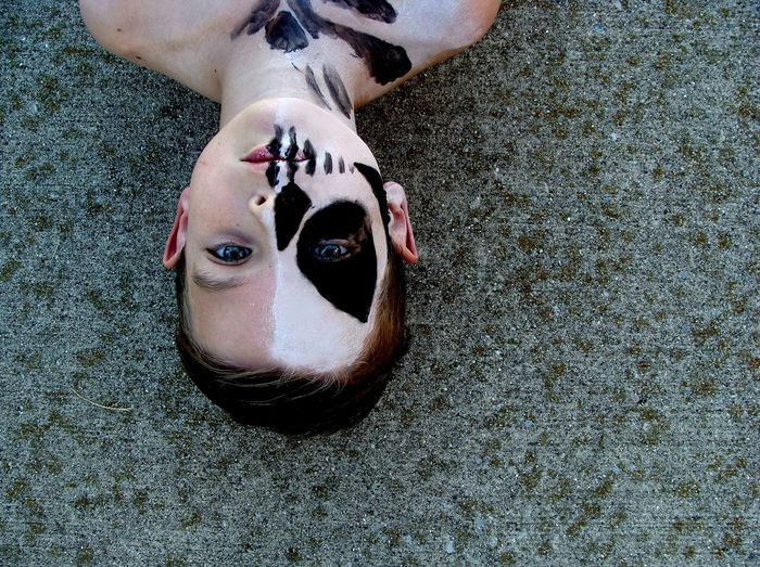 Portrait of shirtless boy with face paint lying on footpath