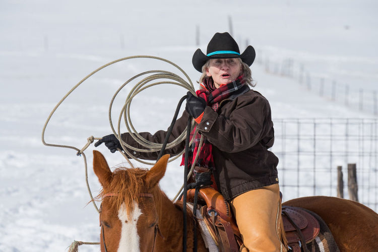 Feb 2019 - Music Meadows Ranch Colorado Ranch Life Cowgirl Cowboy Cowboy Hat Chaps Lassoing Rope Horse Working Animal Warm Clothing Outdoors Horseback Riding Ride Clothing Winter Hat One Animal Domestic Animal Themes One Person Livestock Horse Themes Domestic Animals Real People Riding Animal Mammal