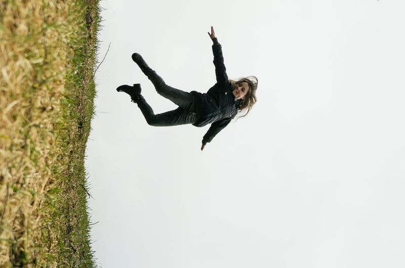Low angle view of woman jumping in mid-air