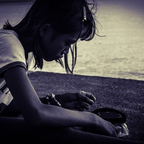 Side View Of Teenage Girl Opening Pouch While Sitting At Lakeshore