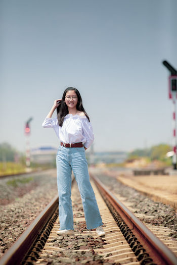 Smiling girl standing on railroad track against clear sky