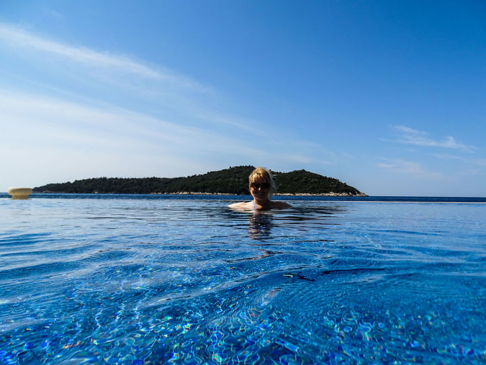 Woman swimming in infinity pool against blue sky