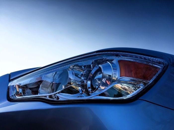 Close-up of car headlight against clear sky