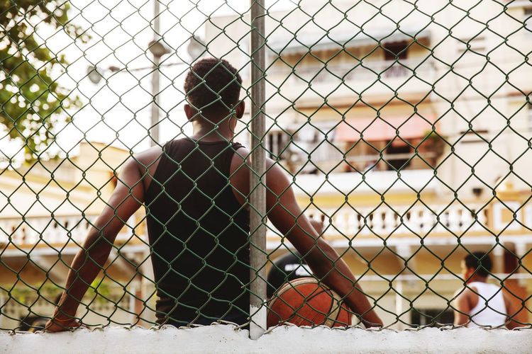 Rear view of woman sitting by chainlink fence