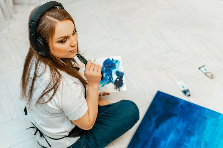 High angle view of thoughtful woman sitting on floor at home