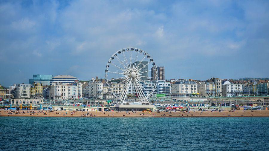 Ferris wheel by sea against cityscape