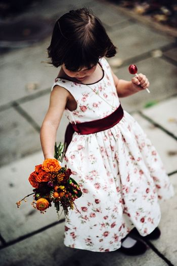 Flower girl with sucker and bouquet Flowergirl Wedding Flowers Lollipop Girl Childhood Girls Women Focus On Foreground Dress Females High Angle View Holding Outdoors Food Standing Clothing Innocence Flower One Person