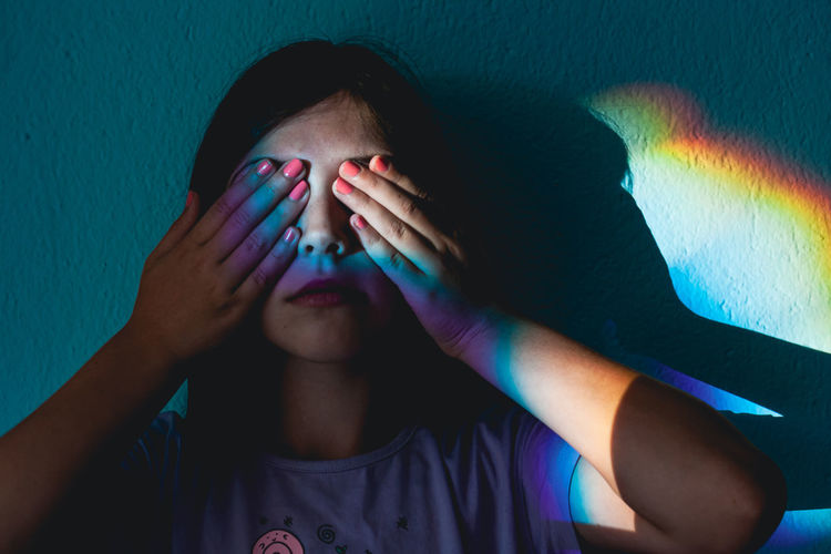 Close-up portrait of girl covering face against blue wall