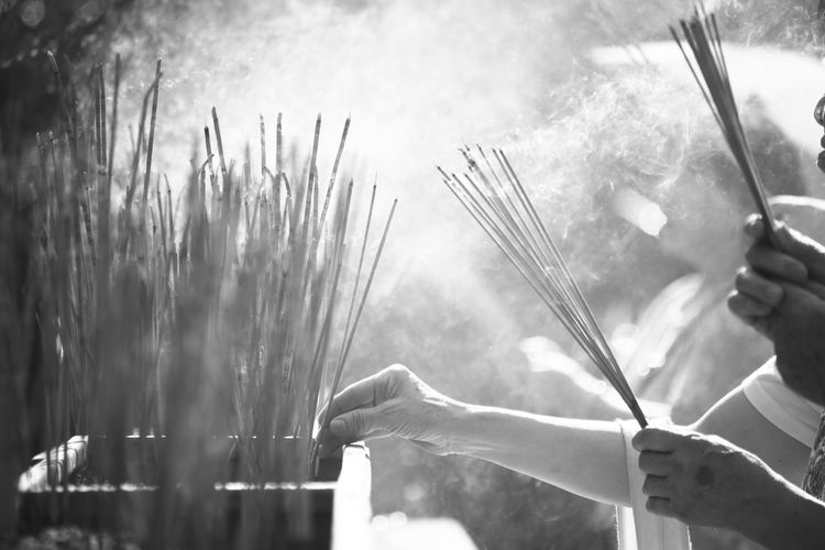 Close-up of human hands holding burning incense stick