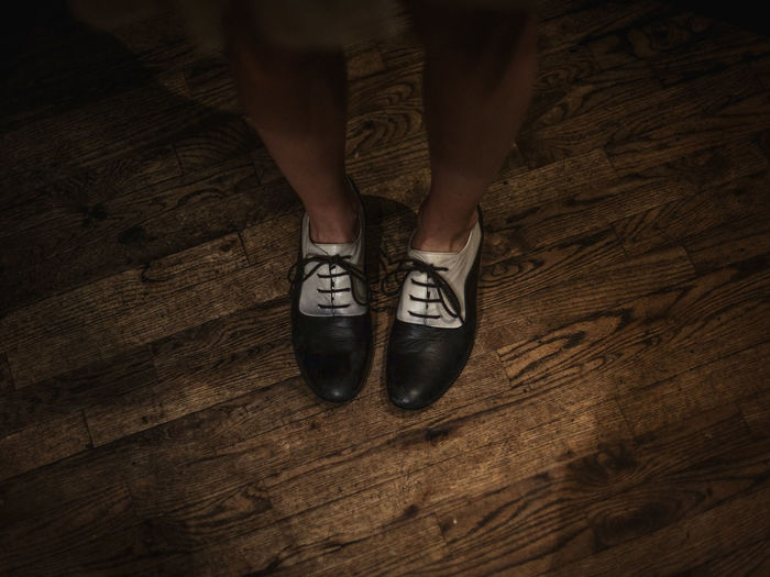 High Angle View Of Woman Wearing Shoes On Hardwood Floor