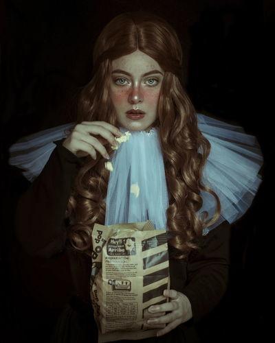 Portrait Of Beautiful Model Having Popcorn Against Black Background