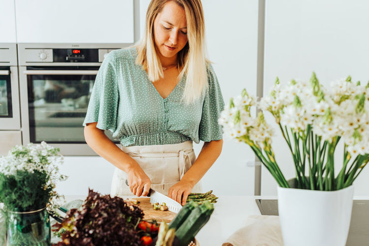 Young woman standing by plants in kitchen