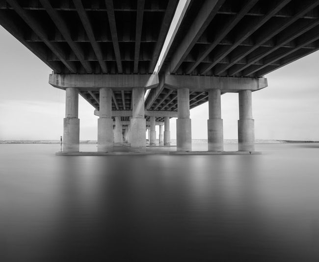 Black and white photo of bridge and river Abstract Architecture Below Black And White Bridge - Man Made Structure Connection Dark In A Row Long Exposure Low Angle View Modern No People Outdoors Pier Reflection River Shadow Skyline Suspension Bridge Transportation Underneath Urban View Water Waterfront