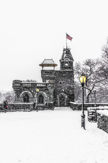 Belvedere Castle covered in snow Central Park Architecture Building Exterior Built Structure Cold Temperature Covering Flag Frozen Incidental People Nature Patriotism Selective Color Sky Snow Snowing Tree Winter
