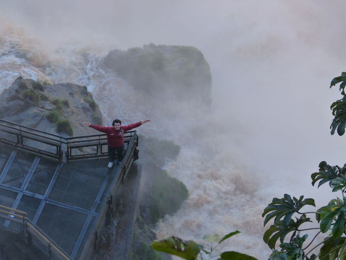 High angle view of man with arms outstretched by iguacu falls