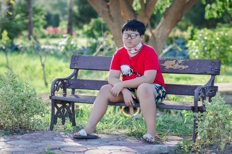 Portrait of boy sitting on bench in park