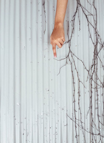 Cropped hand of woman pointing by corrugated iron