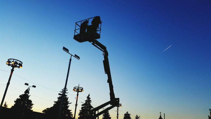 Low angle view of silhouette cherry picker against clear blue sky