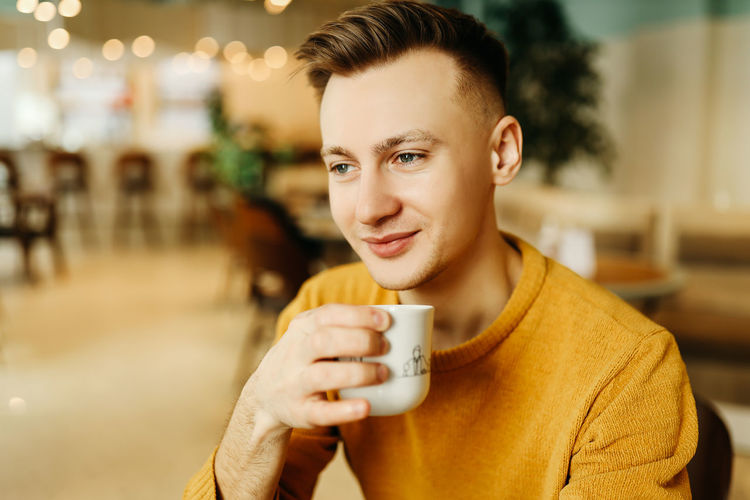 Portrait of smiling man holding coffee cup