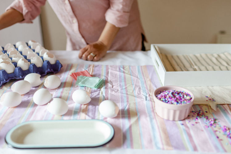 Midsection of woman holding toys on table