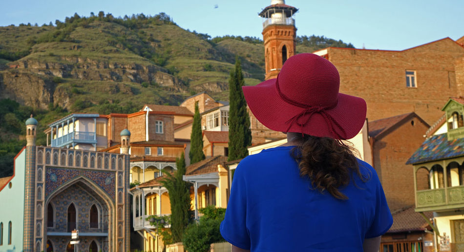 Rear view of woman standing by buildings against mountain
