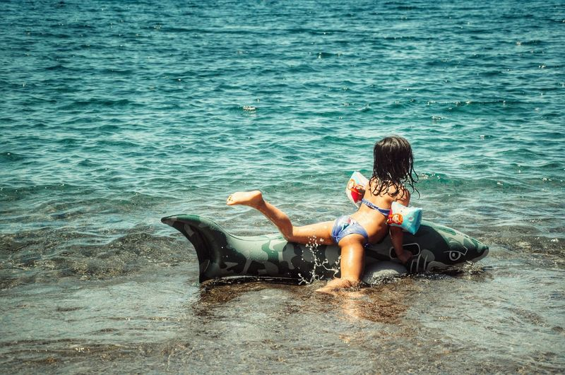 Rear View Full Length Of Playful Girl With Inflatable Fish At Beach