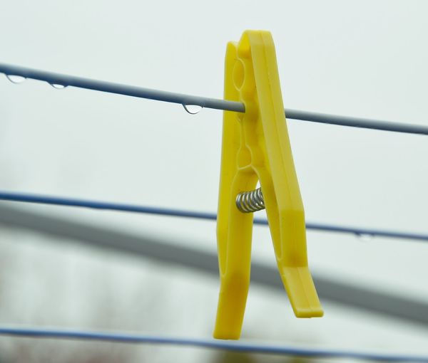 Close-up of yellow clothespin on clothesline