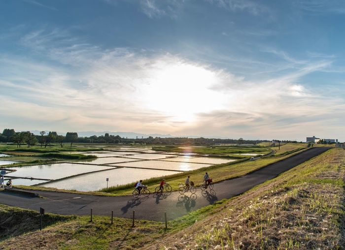 People riding bicycle by field against sky during sunny day