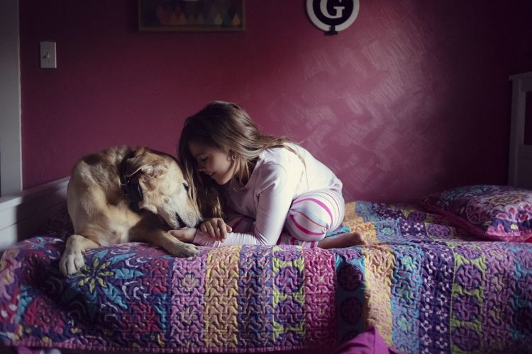Girl with dog on bed at home
