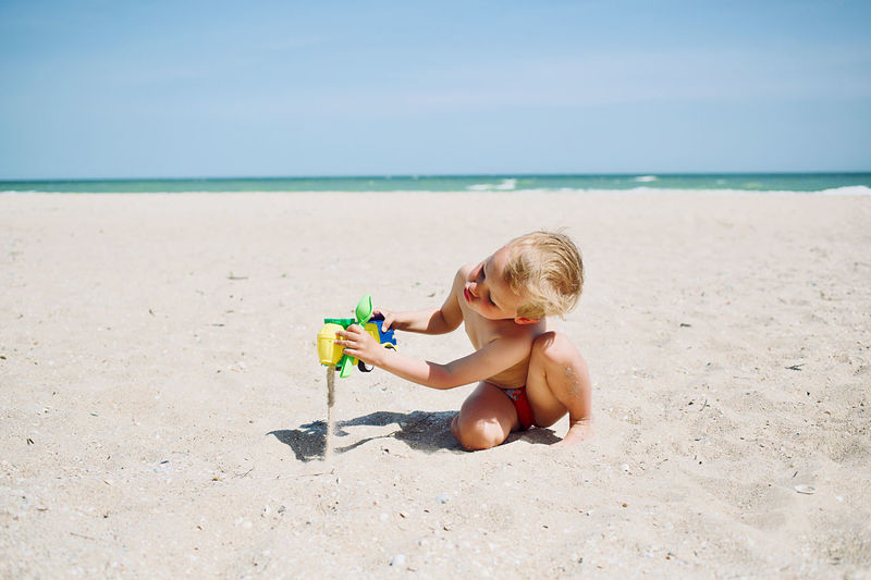 Little boy 3 years old play at sea sandy beach with concrete mixer toy car