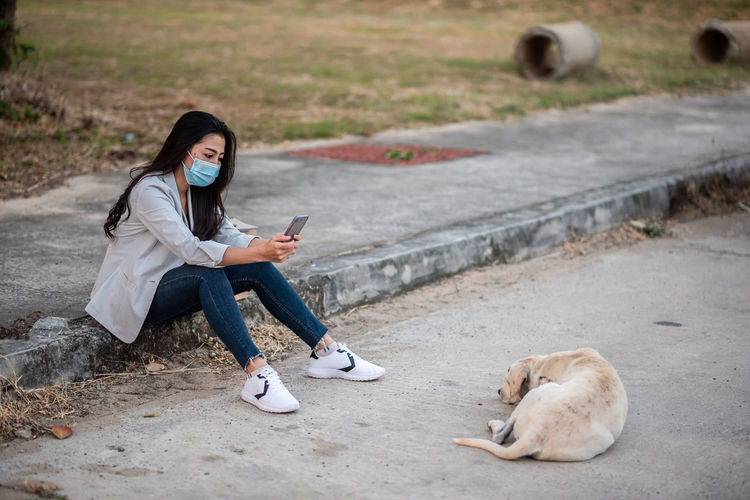 Full length of woman wearing mask photographing dog on road