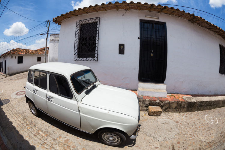 GIRON, COLOMBIA - MAY 3: An old car parked in the street in Giron, Colombia on May 3, 2016. Colombia Exterior Latin America Santander Sunny Travel Architecture Bucaramanga Car Cobblestone Colombian  Colonial Destination Girón Historic House No People Outdoors Sky South America Tourism Transportation Vintage White