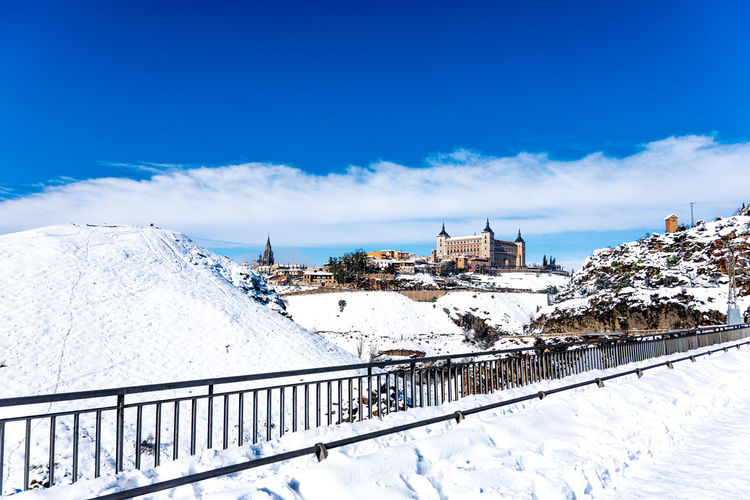 Snow covered buildings against blue sky
