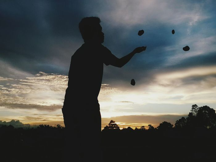 Silhouette Man Juggling With Stone Against Sky